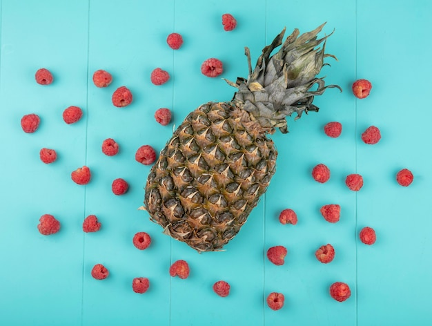 Top view of raspberries with pineapple on blue surface