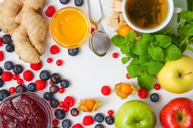 Вид сверху малина с чаем, мед, яблоки, черника, красная смородина, лимон, имбирь, листья мяты на белой поверхности. горизонтальный