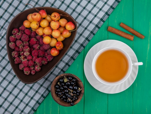 Top view of raspberries with white cherries in a bowl with a cup of tea cinnamon and black currants on a green surface