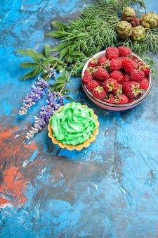 Vista dall'alto della ciotola di lamponi e piccola torta sulla superficie blu