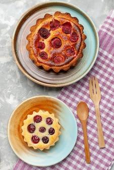 Vista dall'alto torta di lamponi deliziosa con piccola torta sulla torta da scrivania grigio chiaro cuocere dolce alla frutta
