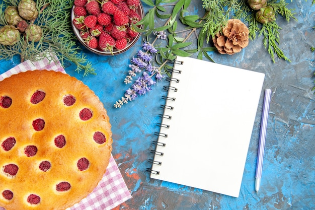 Top view of raspberry cake on kitchen towel bowl with raspberries pine tree branch a pen a notebook on blue surface