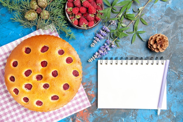 Top view of raspberry cake on kitchen towel bowl with raspberries pine tree branch a pen on notebook on blue surface