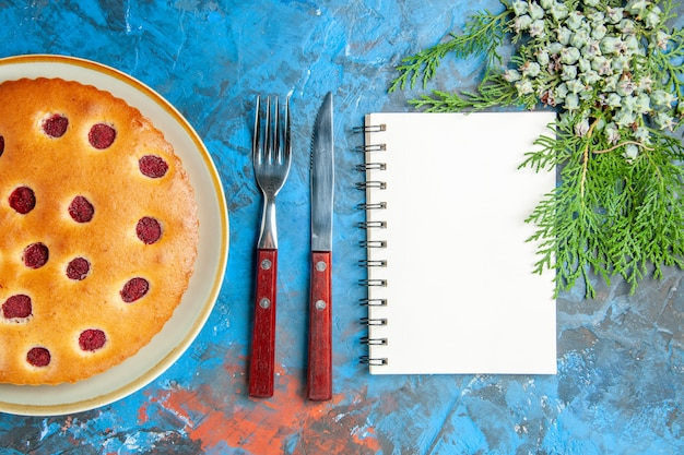 Top view of raspberry cake on oval plate cones fork knife a notebook on blue surface