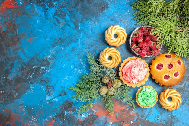 Top view of raspberry cake, small tarts, biscuits, bowl with berries and tree branches on blue surface
