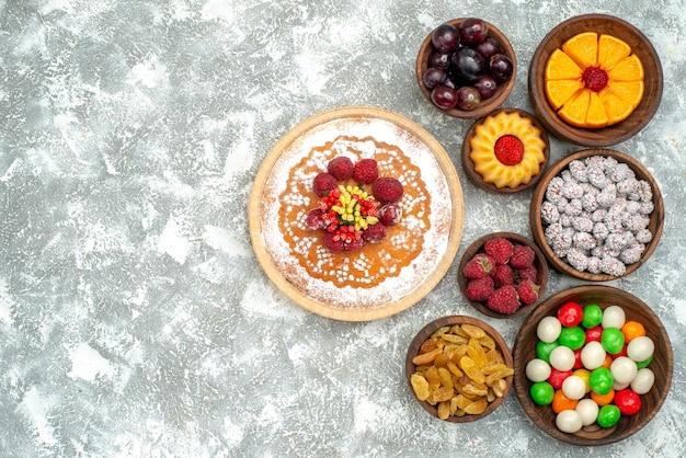 白い表面のフルーツビスケットケーキパイにキャンディーとレーズンの上面図ラズベリーケーキ