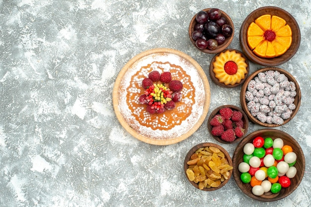 Torta di lamponi vista dall'alto con caramelle e uvetta su torta di biscotto alla frutta con superficie bianca