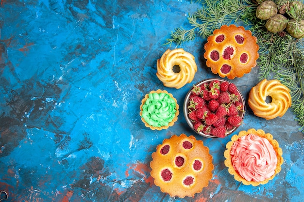 Top view of raspberry cakes, biscuits, small tarts, cones and bowl with strawberries on blue surface