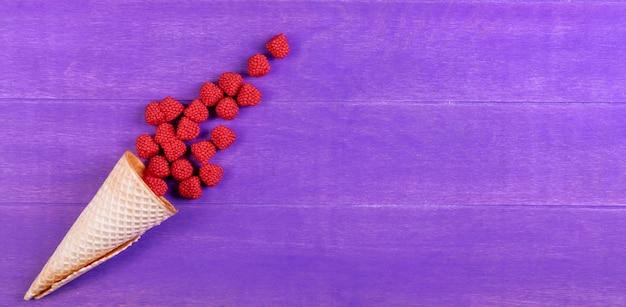 Вид сверху малиновый мармелад с вафельным рожком на фиолетовом фоне