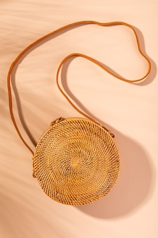 Top view of rattan bag on pastel yellow background, flat lay