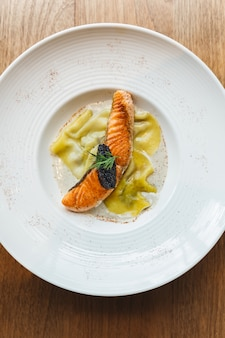 Top view of ravioli in cream sauce with grilled salmon topping with caviar.