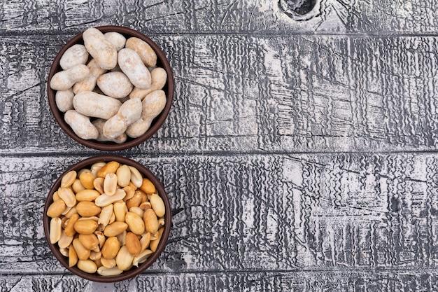 トップビューコピースペースと木製のボウルに生とフライドピーナッツ