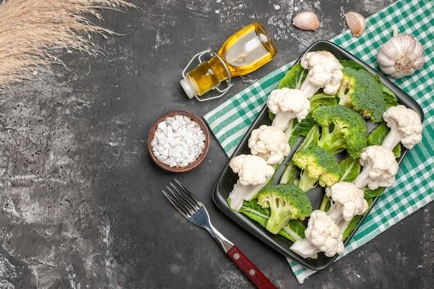 Вид сверху сырой брокколи и цветной капусты на черной прямоугольной тарелке на зеленой и белой клетчатой салфетке, вилка, масло, чеснок, морская соль на темной поверхности, свободное пространство
