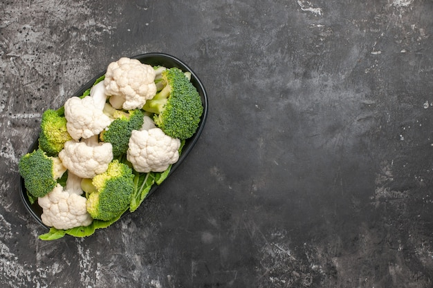Top view raw broccoli and cauliflower on black oval plate on dark surface with copy space