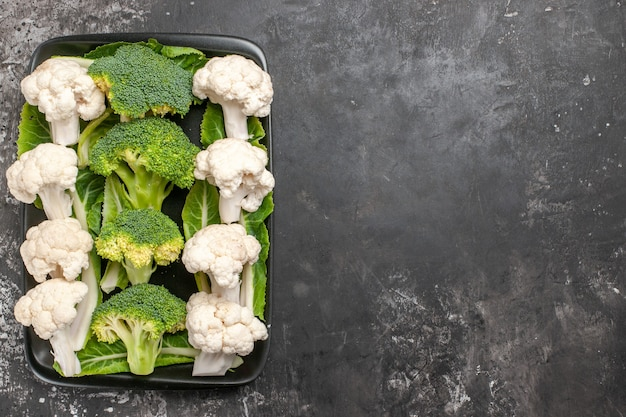 Top view raw broccoli and cauliflower on black rectangular plate on dark surface free space