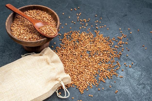 Vista dall'alto di grano saraceno crudo dentro e fuori la borsa sullo spazio grigio