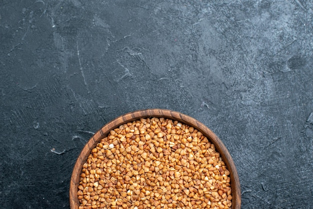 Top view raw buckwheat useful product inside plate on the dark space