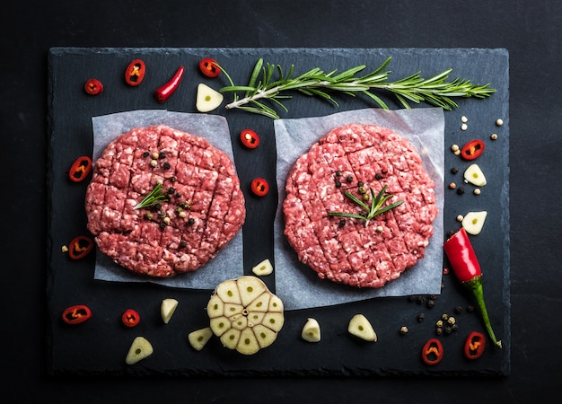 Top view of raw burger cutlets with spicies