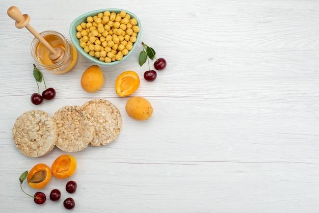 Вид сверху сырые хлопья внутри тарелки с крекерами, фруктами и медом на белом, пить молоко, молочные сливки, завтрак