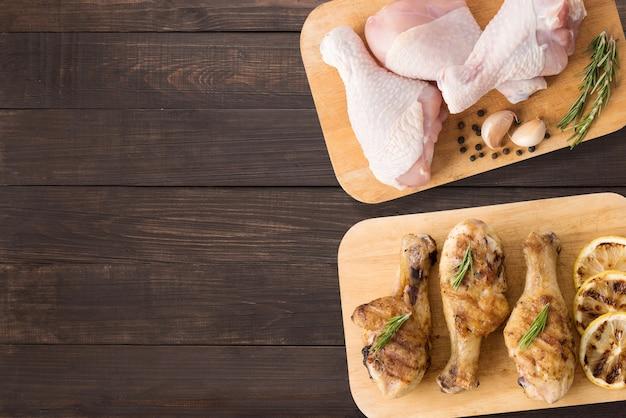 木製の背景にまな板の上の生鶏とグリルチキンの平面図です。テキストのコピースペース