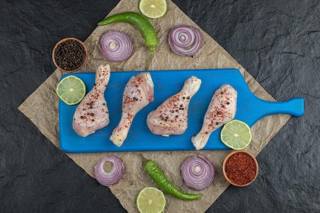 Вид сверху сырые куриные голени и свежие овощи и специи.