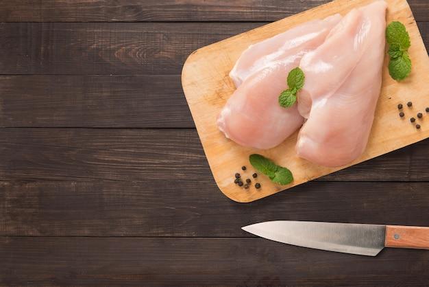まな板と木製の背景にナイフでトップビュー生鶏。テキストのコピースペース