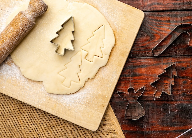 Top view of raw dough and christmas cookie cutters on rustic kitchen table