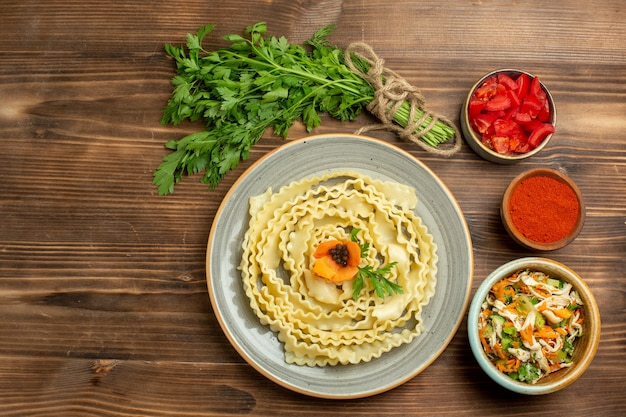 Top view raw dough designed pasta with greens and seasonings on brown background pasta dough food meal vegetable