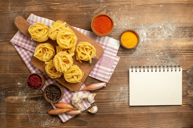 Top view raw dough flower formed pasta with seasonings on wooden background dough food pasta