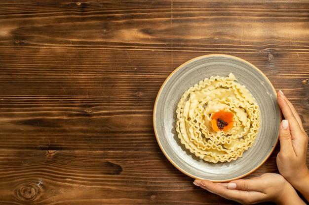 Vista dall'alto pasta di pasta cruda formata all'interno del piatto sul pasto di pasta di cibo crudo di pasta da tavola marrone