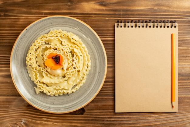 Vista dall'alto pasta di pasta cruda formata all'interno della piastra sul pasto di pasta di cibo crudo di pasta da tavola in legno marrone