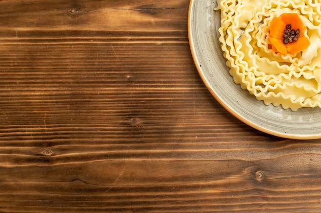 Вид сверху макароны из сырого теста, сформированные внутри тарелки на коричневом столовом тесте, пищевые макароны