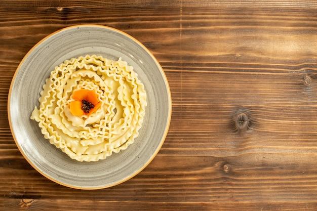 Вид сверху макароны из сырого теста, сформированные внутри тарелки на коричневом столовом тесте, макароны из сырой пищи