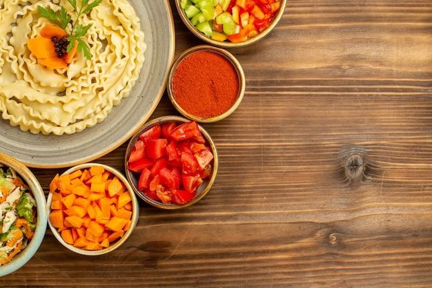 茶色のテーブル生地のローフードパスタミールに野菜と調味料で形成された上面図生生地パスタ
