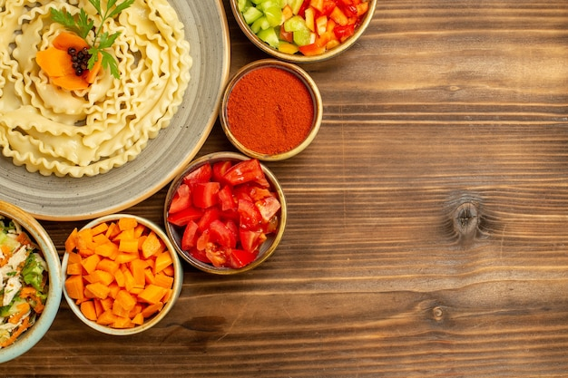 Vista dall'alto pasta di pasta cruda formata con verdure e condimenti sul pasto di pasta di cibo crudo di pasta da tavola marrone