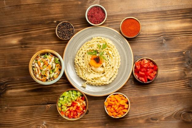 Vista dall'alto pasta di pasta cruda formata con verdure e condimenti su pasta da tavola marrone di cibo crudo