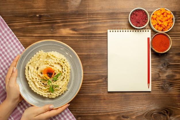 茶色のテーブル生地のローフードパスタミールにさまざまな調味料を加えた上面図生生地パスタ