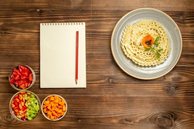 茶色の木製の背景にさまざまな調味料を使用した上面図生生地パスタ生地食品パスタミール