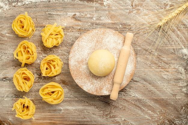 木製の茶色の背景に小麦粉と生地の食事食品パスタの上面図生生地パスタ