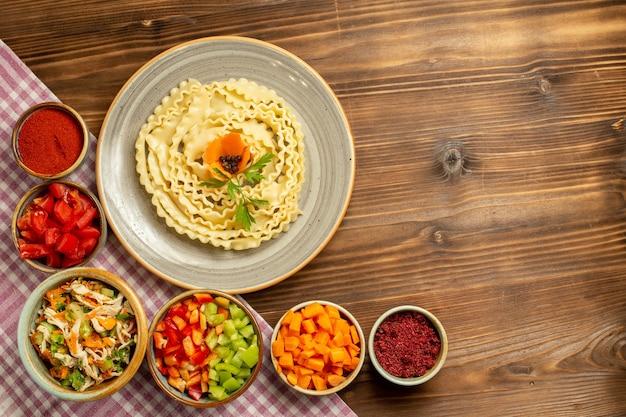 茶色のテーブルに野菜と調味料を入れたトップビュー生生地パスタ生地ローフードパスタミール