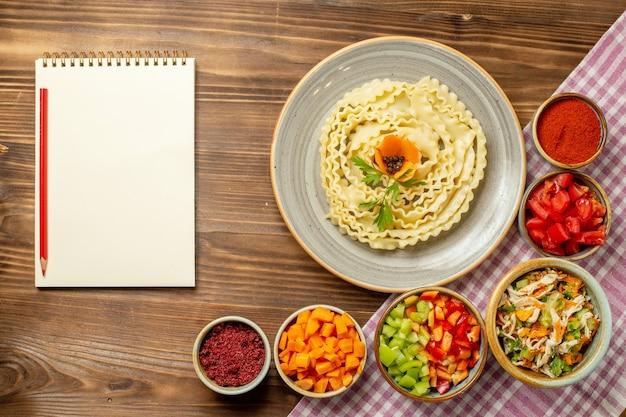 Vista dall'alto pasta di pasta cruda con verdure e condimenti sul pasto di pasta alimentare di pasta da tavola marrone
