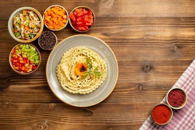 Vista dall'alto pasta di pasta cruda con verdure e condimenti sul pasto di pasta di cibo crudo di pasta da tavola marrone