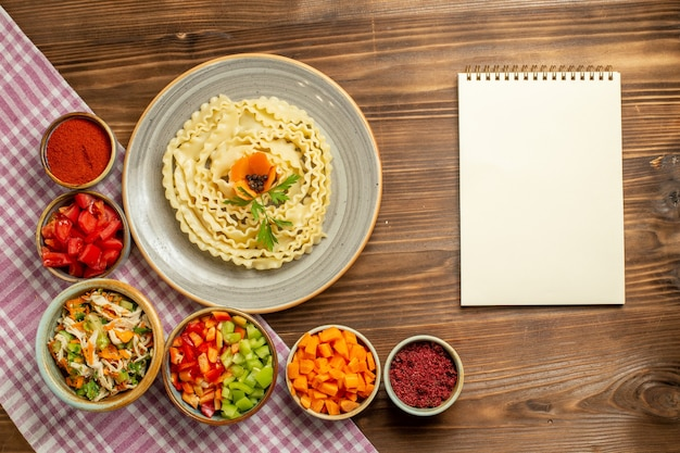 Top view raw dough pasta with vegetables and seasonings on the brown table dough raw food pasta meal