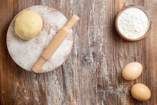 木製の素朴な机の上の小麦粉と小麦粉の上面図生生地片食事小麦粉焼き生地
