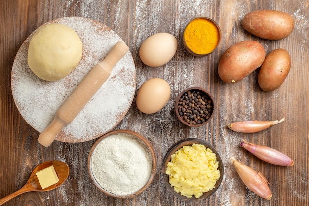 Pezzo di pasta cruda vista dall'alto con farina di patate e uova su farina di farina da scrivania in legno cuocere il colore dell'impasto