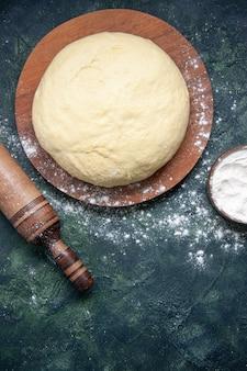 Vista dall'alto pezzo di pasta cruda con farina bianca su sfondo blu scuro pasticceria cuocere torta torta cruda pasta fresca al forno hotcake