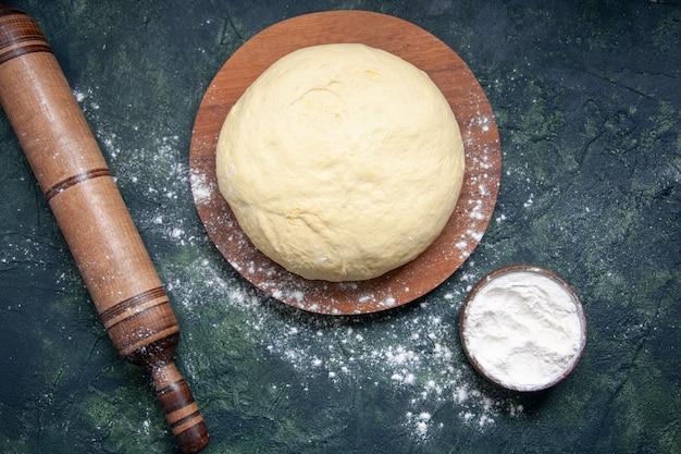 Вид сверху кусок сырого теста с белой мукой на темно-синем фоне, выпечка, торт, пирог, сырое свежее тесто для духовки, горячий пирог