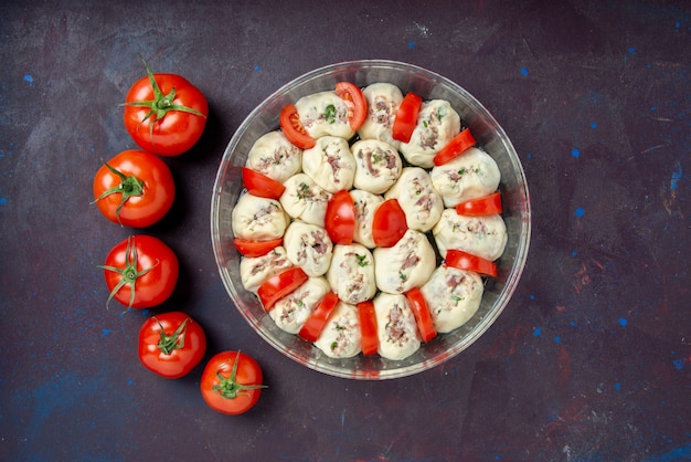 Top view raw dough pieces with ground meat and fresh red tomatoes on dark bake cuisine color photo