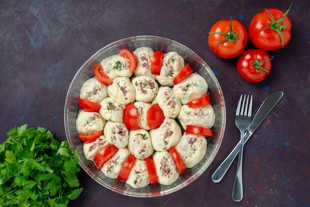 Vista dall'alto pezzi di pasta cruda con carne macinata e pomodori rossi freschi su un pasto scuro cucina colore cibo foto piatto cucina