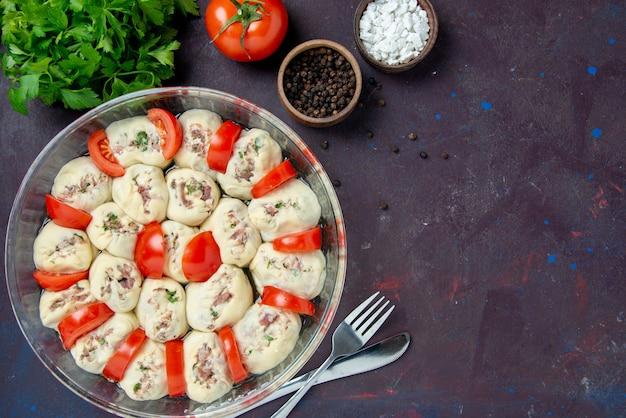 Vista dall'alto pezzi di pasta cruda con carne macinata e pomodori rossi freschi su pasto scuro cucina insalata colore cibo piatto cucina foto